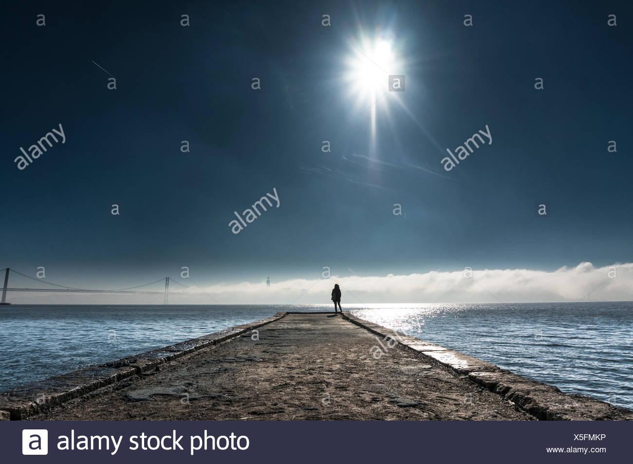 Vista la distanza della persona in piedi sul molo su mare contro Sky Immagini Stock