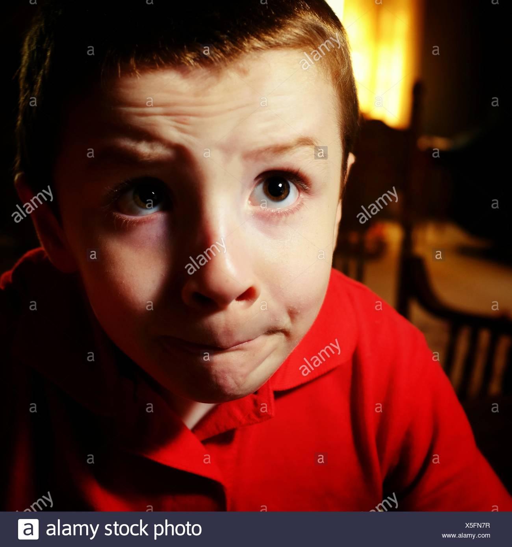 Close-Up di pensosa Boy in casa Immagini Stock