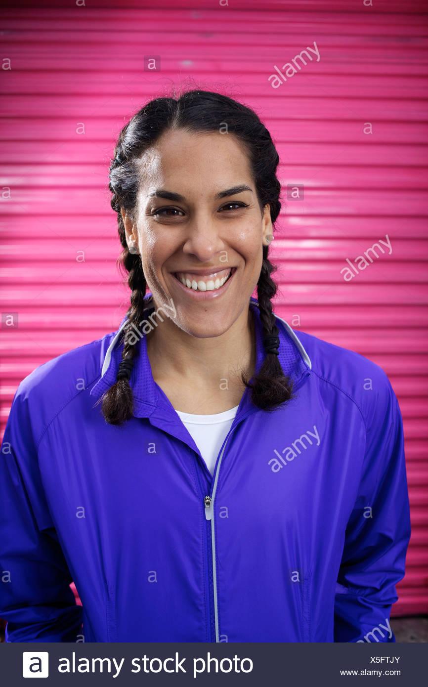 Giovani femmine runner indossa trecce e una giacca blu sorge di fronte a una porta rosa e sorrisi a San Diego. Immagini Stock