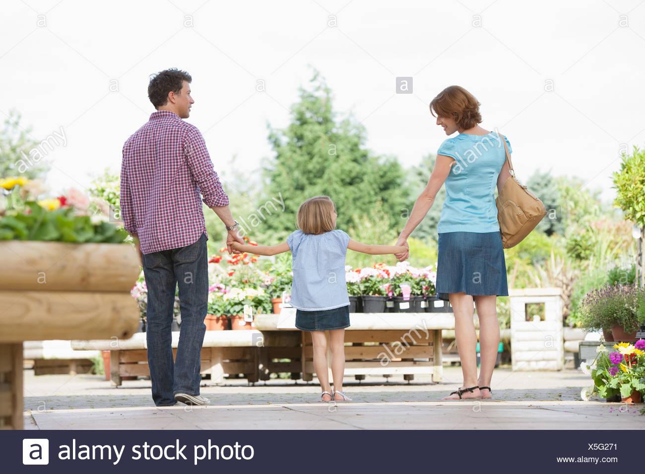 I genitori tenendo la mano figlia in vivaio Immagini Stock