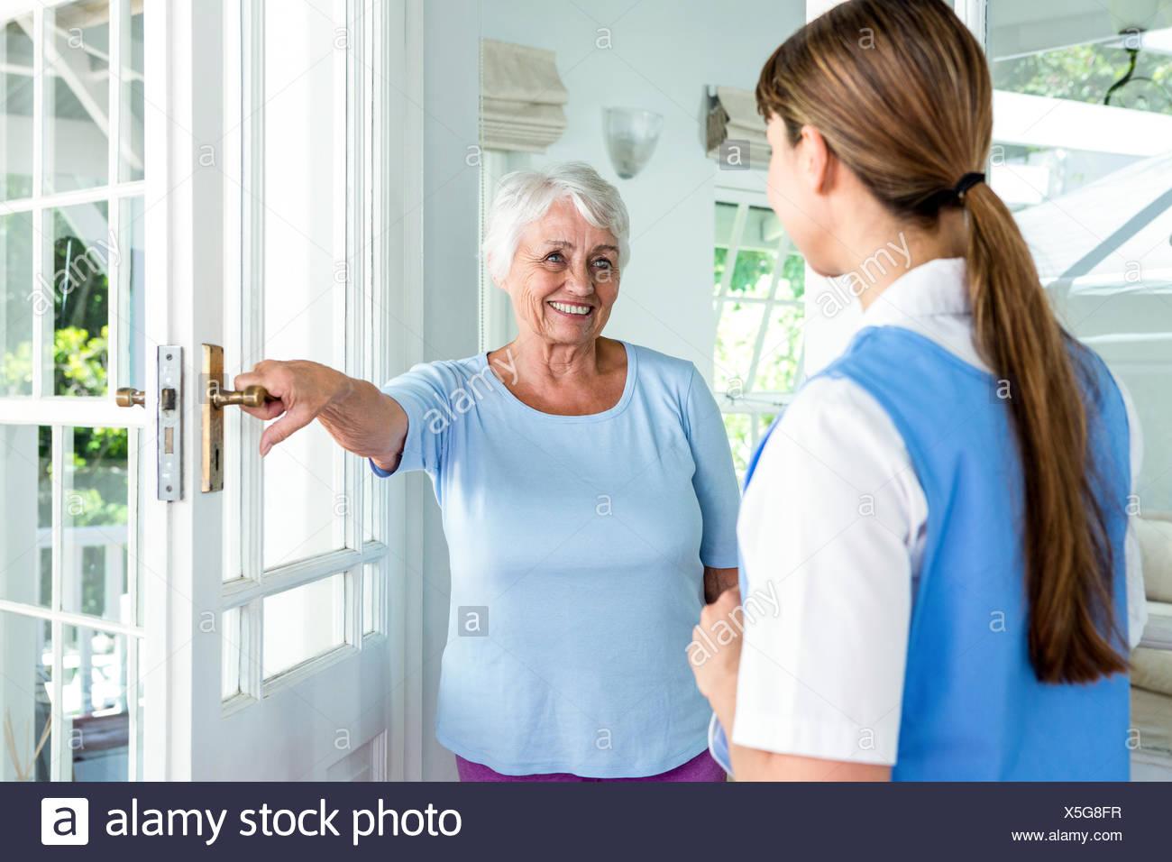 Felice di età donna infermiera permanente Immagini Stock