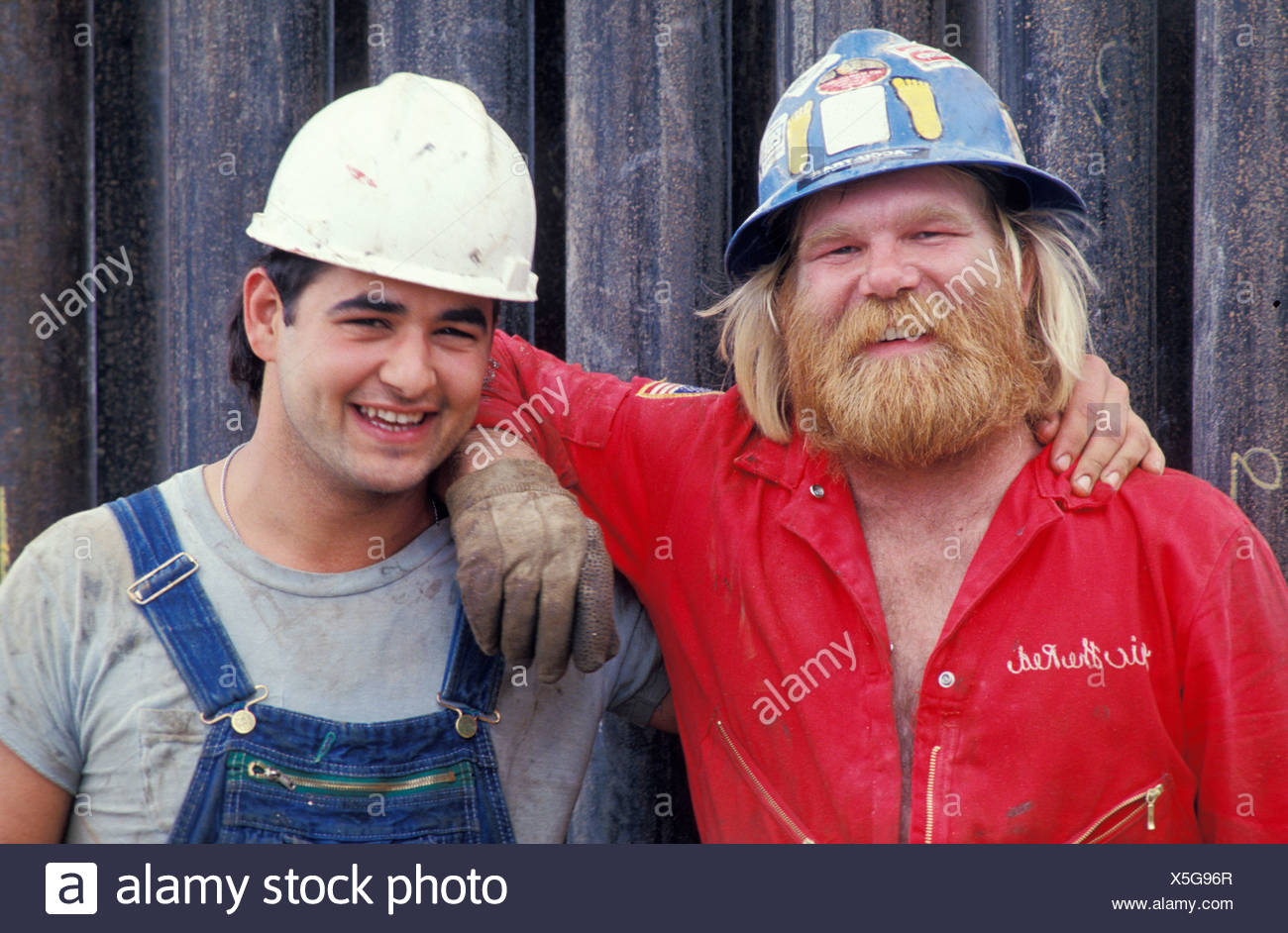 Operai in hard-cappelli sul sito in costruzione sorridente e posa per ritratto Immagini Stock