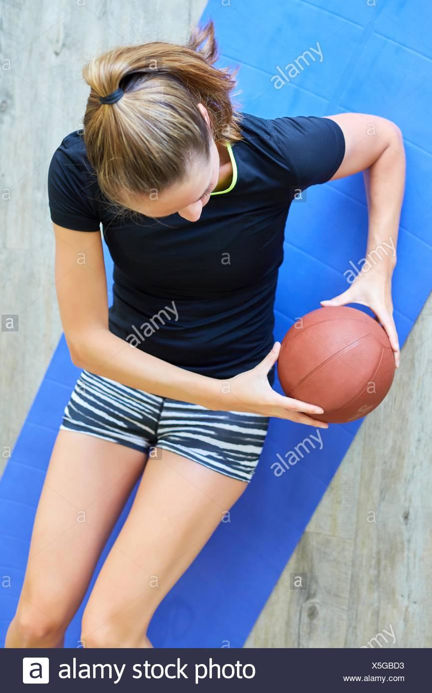 Donna facendo sit ups con sfera in palestra Immagini Stock