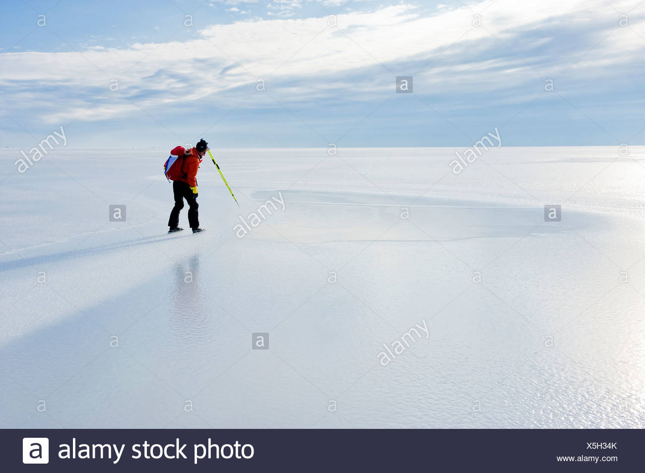 Vista laterale di un pattinatore sul tranquillo lago ghiacciato contro il cielo nuvoloso Immagini Stock