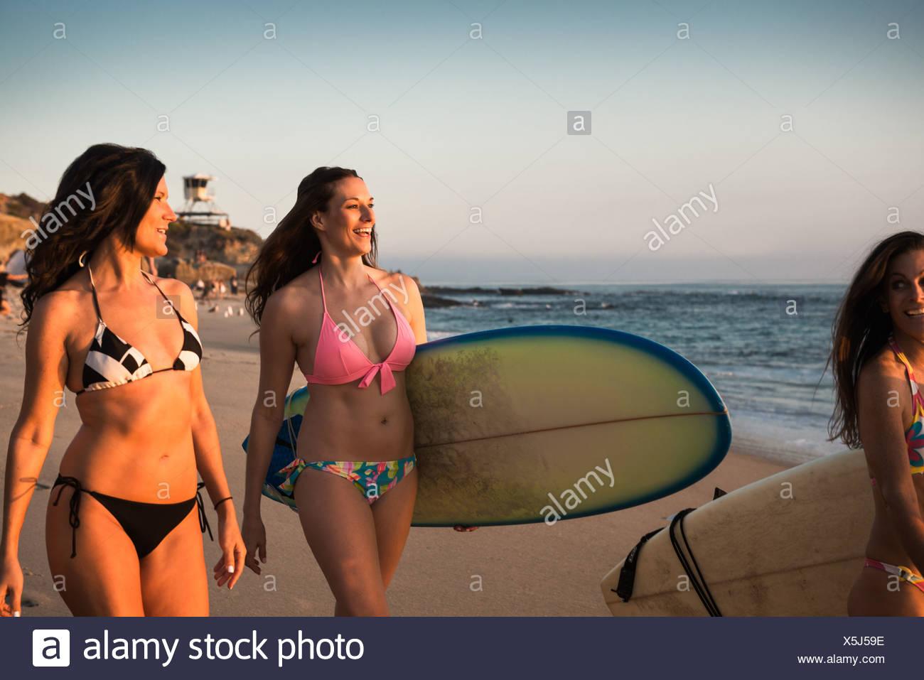 Surfers che trasportano tavole da surf, passeggiate lungo la spiaggia Immagini Stock