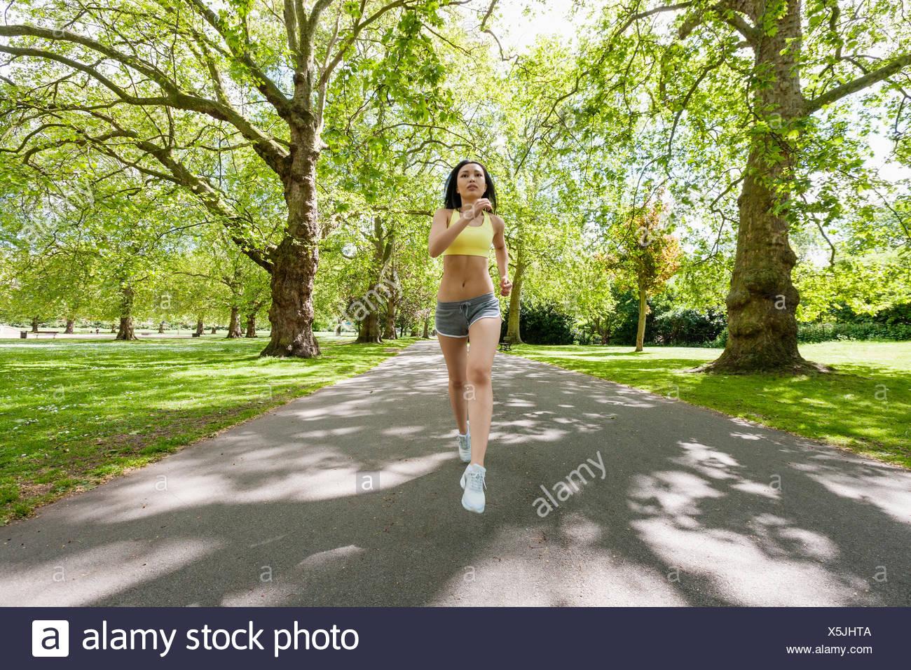 Pieno di lunghezza determinata montare donna jogging al parco Immagini Stock