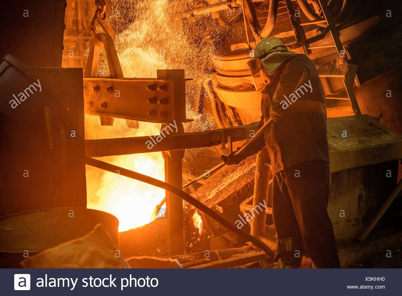 Lavoratore di acciaio guardando giù al forno in fonderia di acciaio Immagini Stock