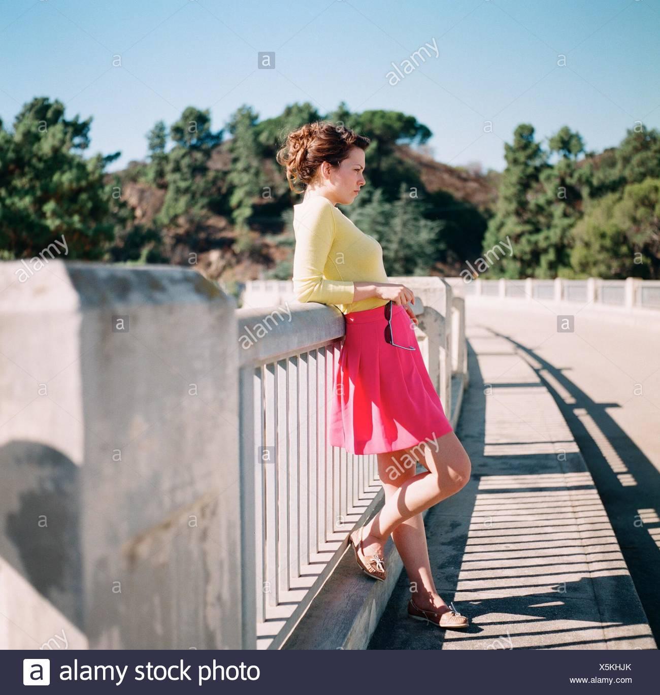 Lato di un grave giovane donna in piedi all'aperto Immagini Stock