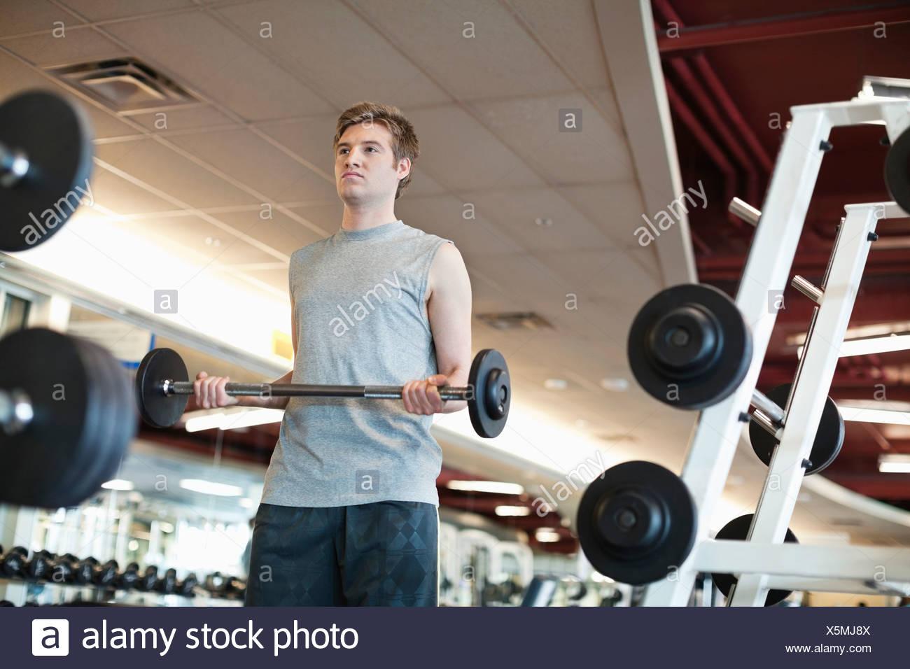 Basso angolo di visione dell'uomo sollevamento pesi nel centro fitness Immagini Stock