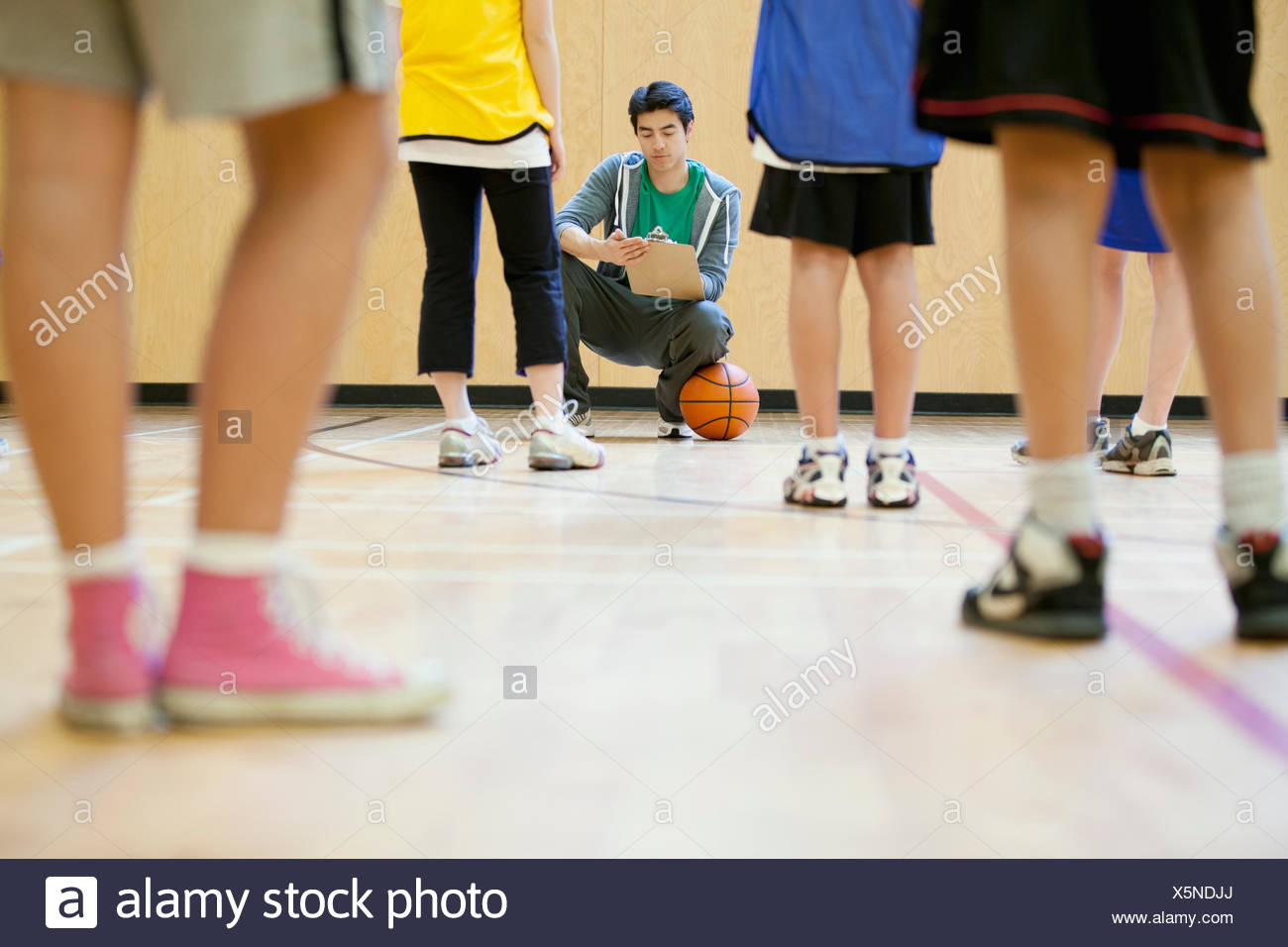 Gli studenti delle scuole medie di ottenere istruzioni su basket Immagini Stock
