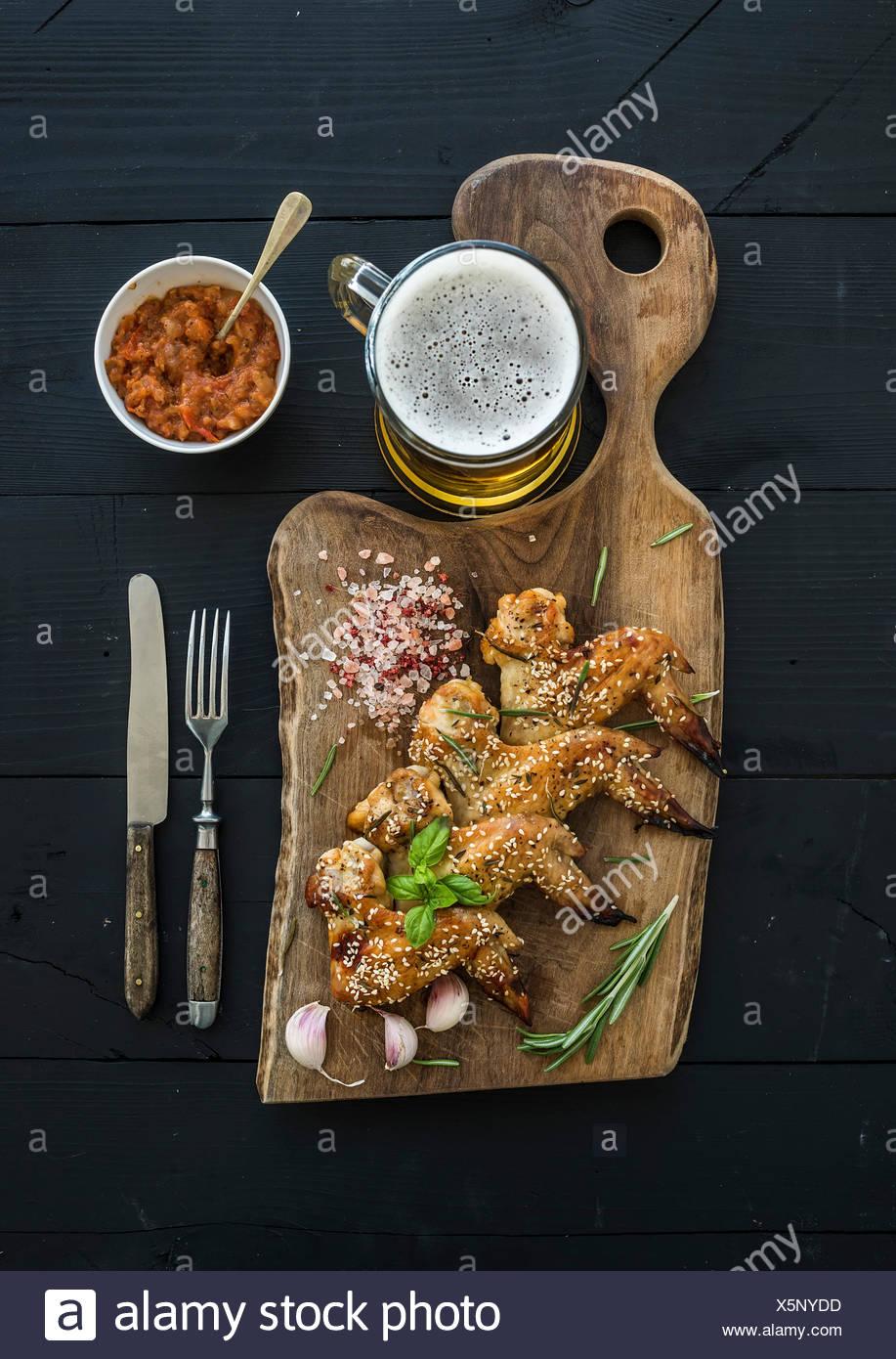Alette di pollo fritte rustico che serve board, piccante salsa di pomodoro, erbe aromatiche e bicchiere di birra chiara su legno nero, sfondo top vie Immagini Stock