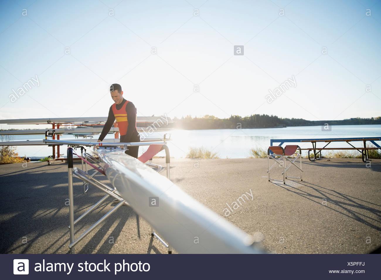 Rematore con scull a waterfront Immagini Stock