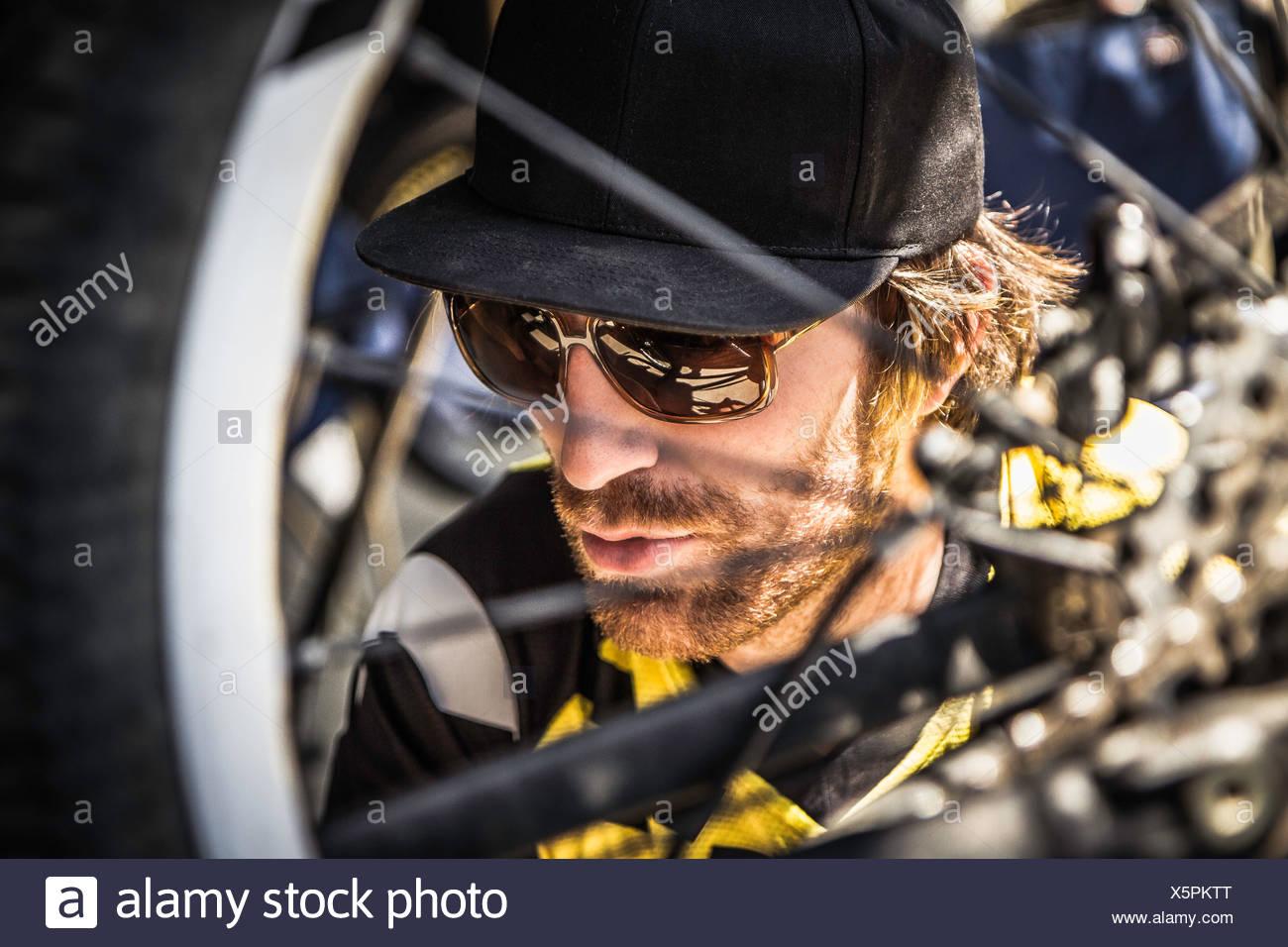 Chiusura del giovane maschio mountain biker controllo ruota di bicicletta Immagini Stock