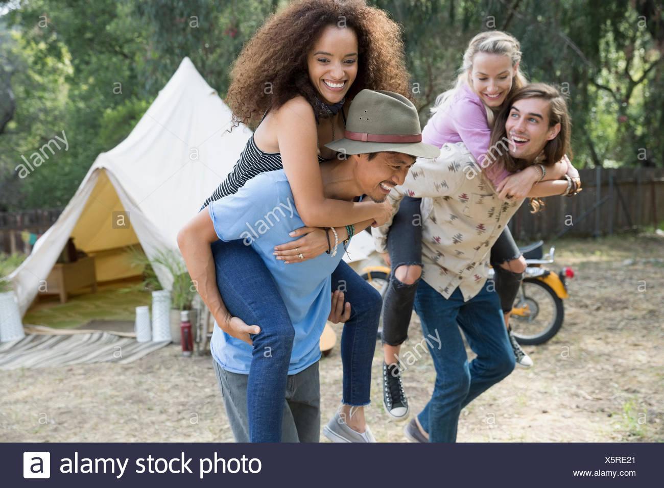 Coppie giovani piggybacking fuori camping yurt Immagini Stock