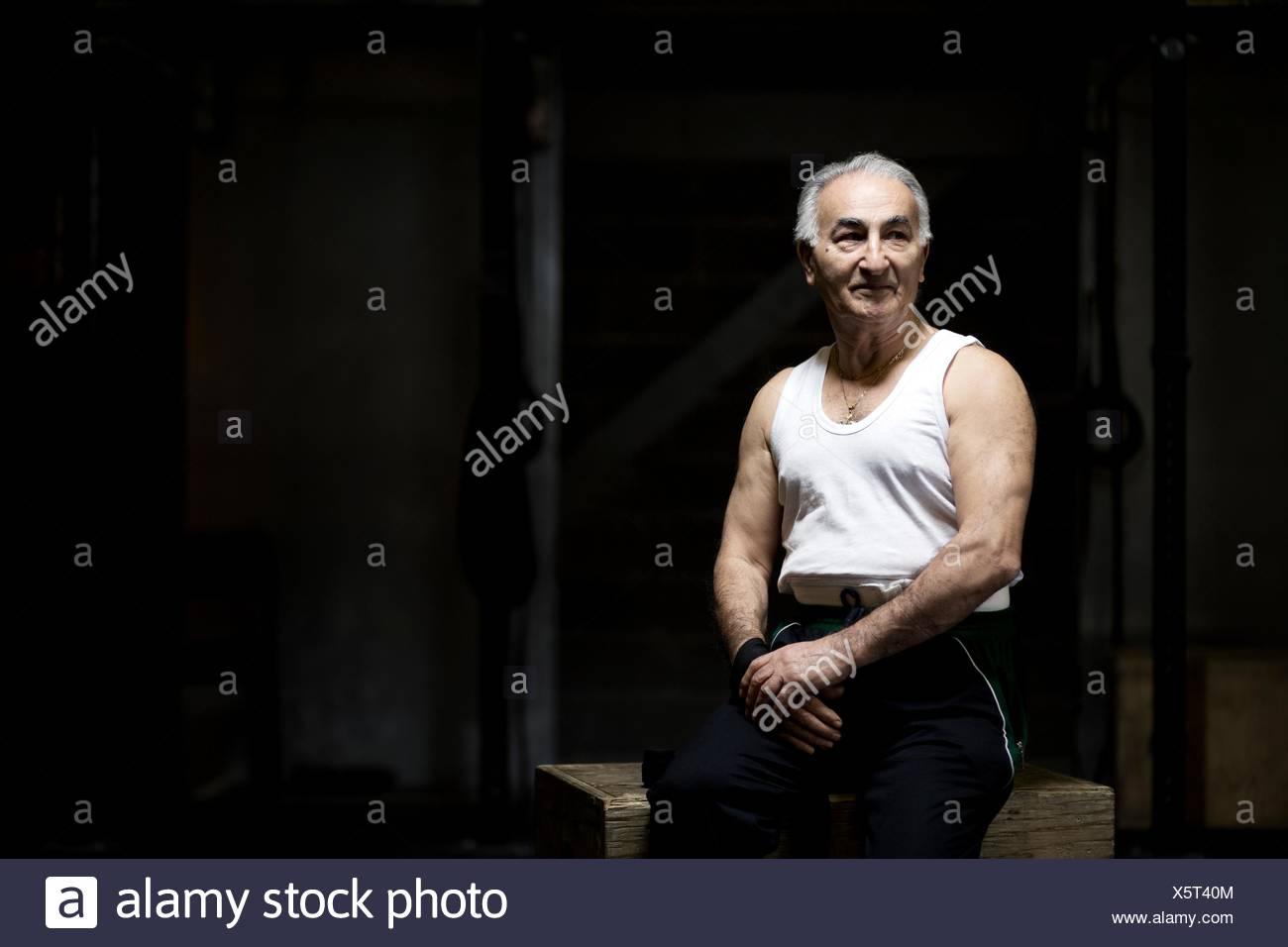 Ritratto di capelli grigi senior uomo seduto nel buio della palestra Immagini Stock