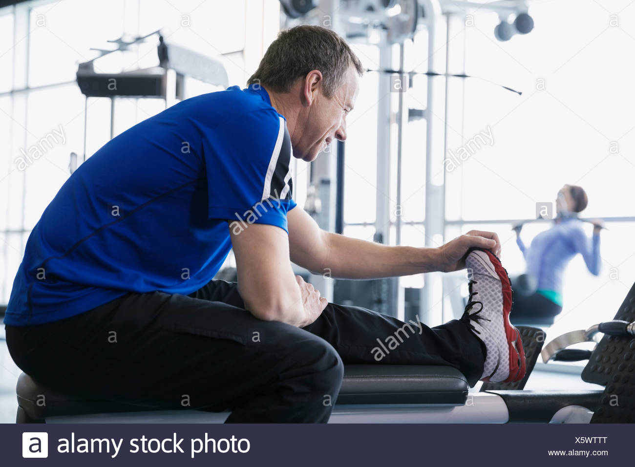 L uomo lo stiramento gamba alla palestra Immagini Stock