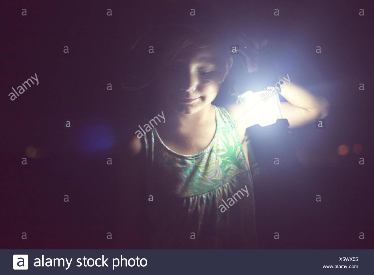 Ragazza con lampada nel buio Immagini Stock
