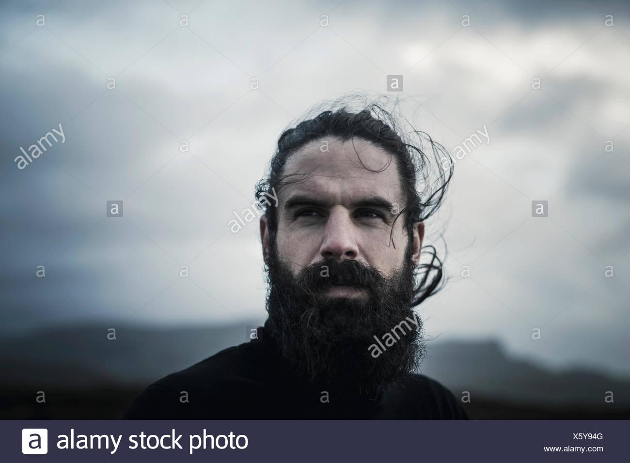 Un uomo con i capelli neri un pieno di barba e baffi. Immagini Stock