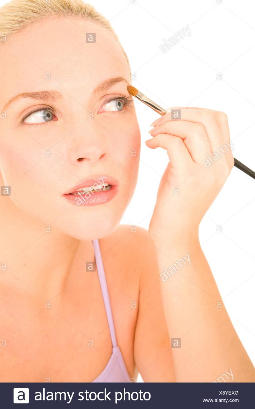 Donna applicando ombretto Immagini Stock