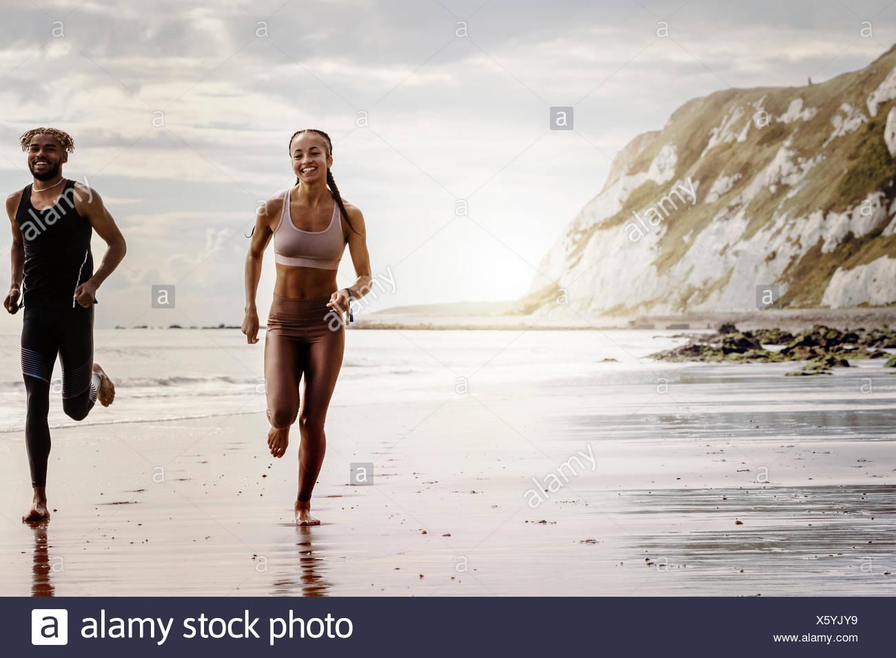 I giovani di sesso maschile e femminile correre a piedi nudi sulla spiaggia Immagini Stock
