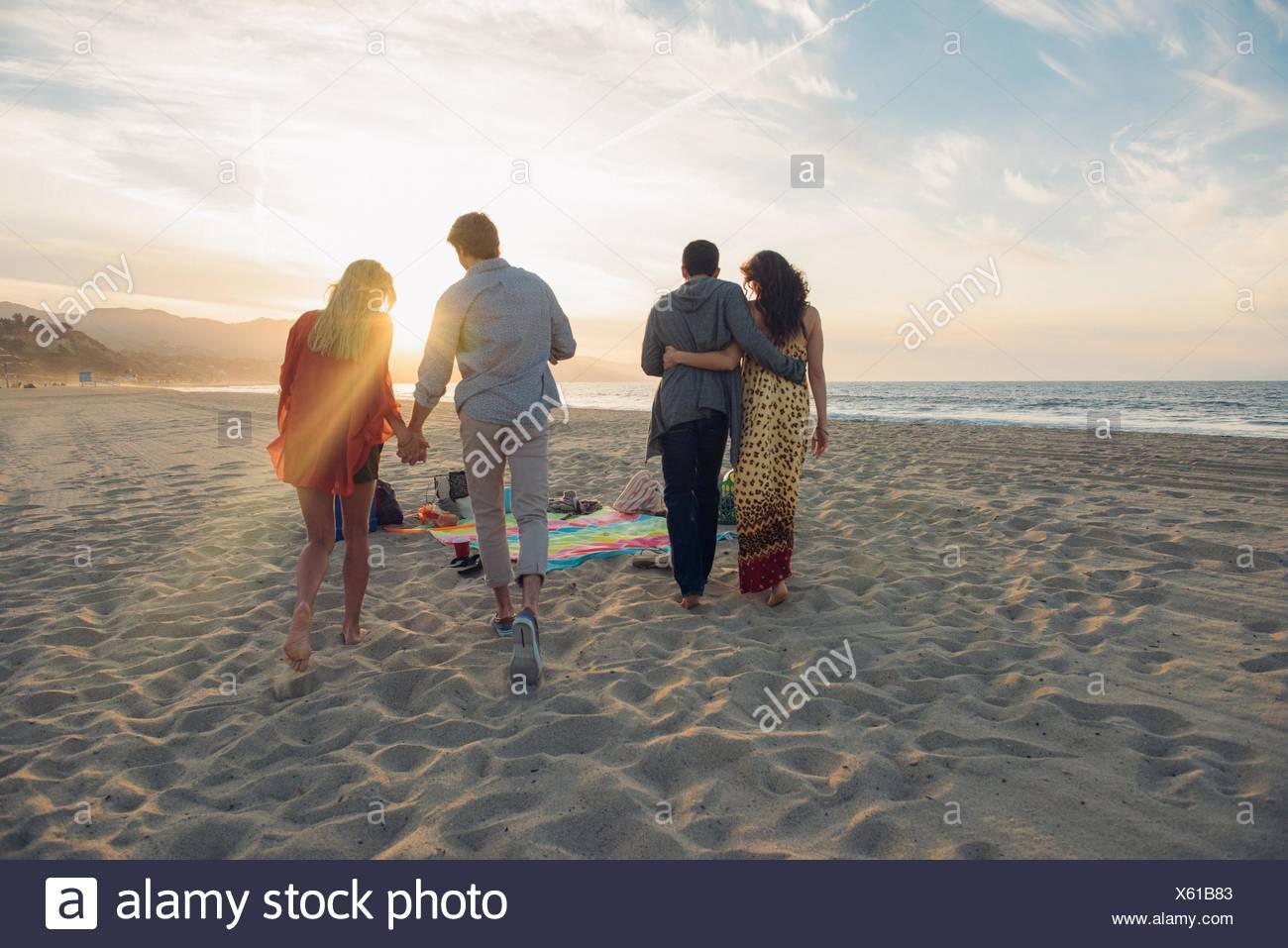 Due giovani coppie camminando lungo la spiaggia, vista posteriore Immagini Stock