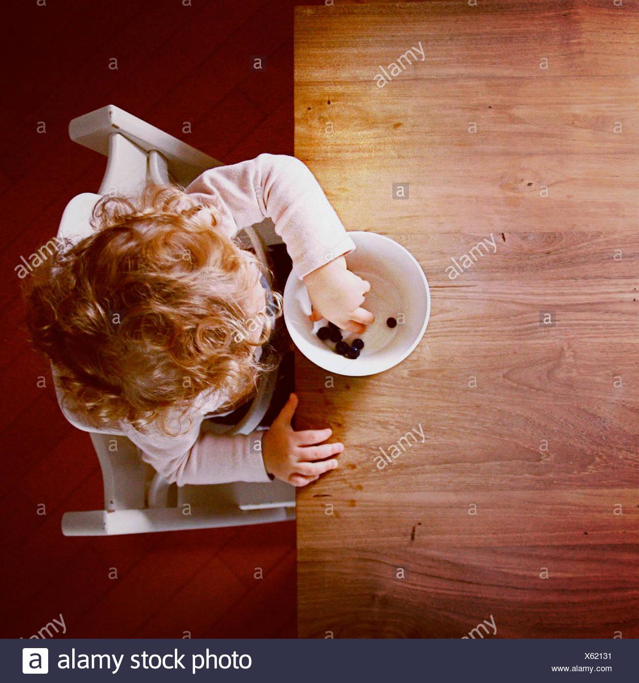 Vista aerea della ragazza (2-3) mangiare mirtilli Immagini Stock