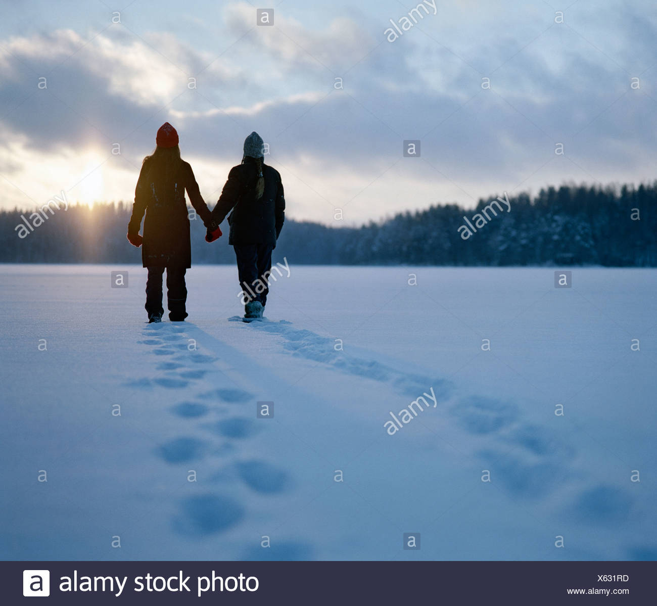 Silhouette di due giovani donne in piedi nella neve in Finlandia Immagini Stock