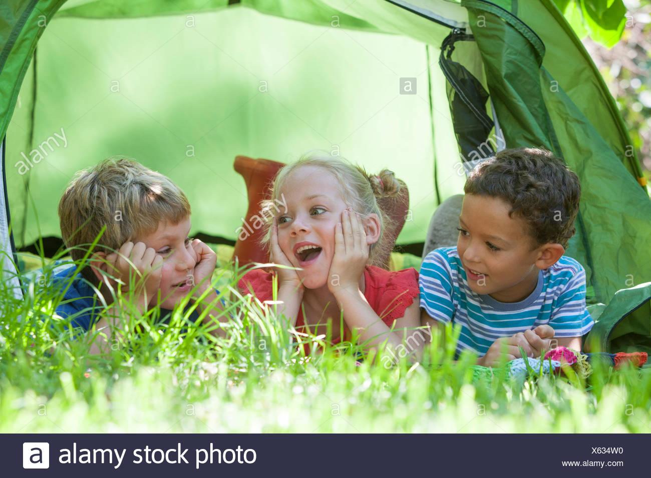 Tre bambini che giace in chat con tenda da giardino Immagini Stock