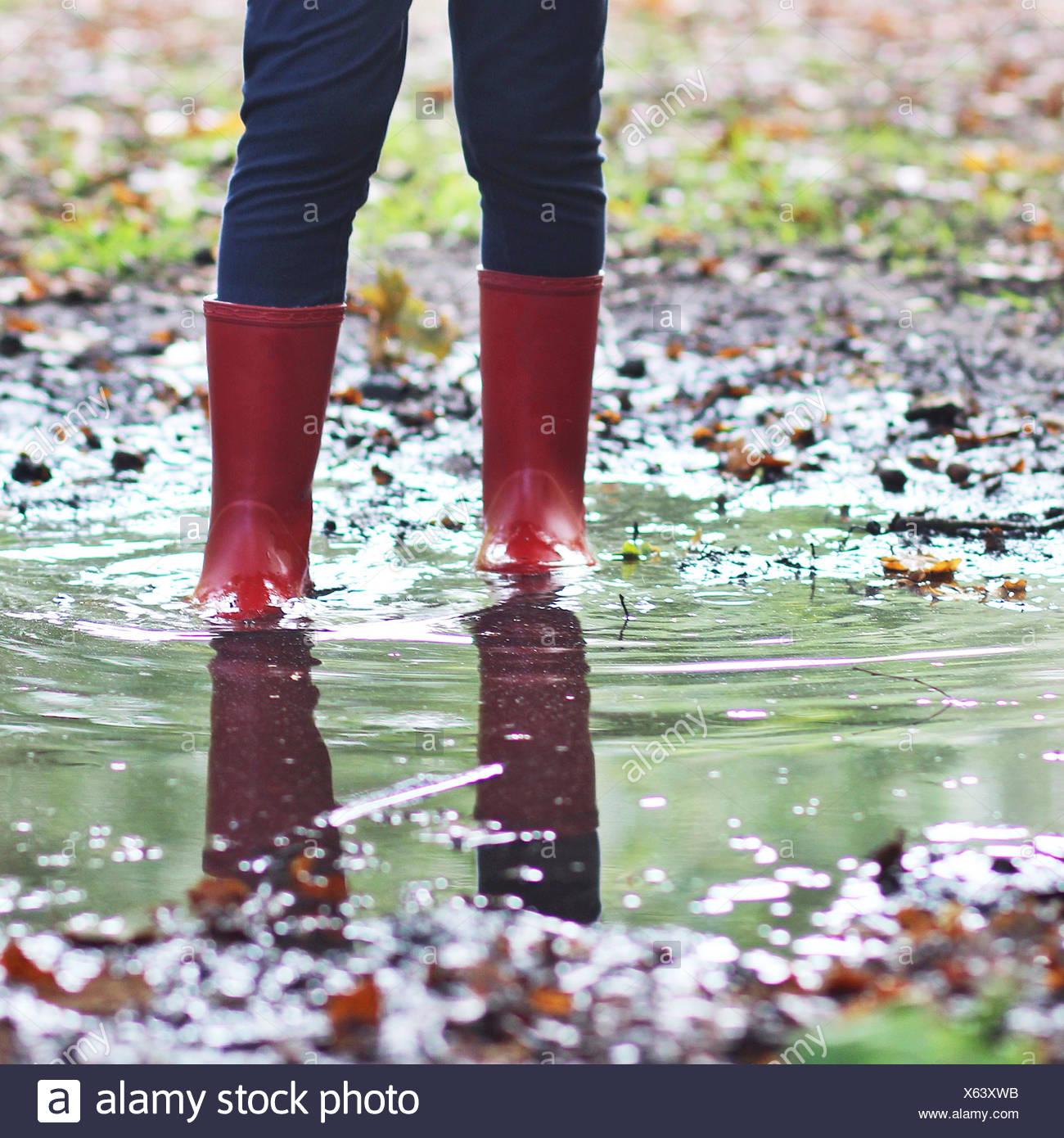 Ragazza di indossare gli stivali da pioggia in piedi in una pozza Immagini Stock
