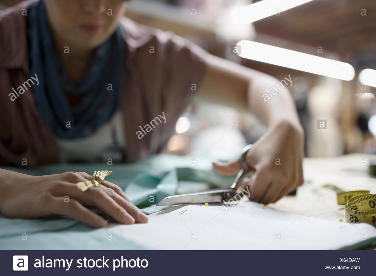 Femmina designer di moda il taglio di tessuto con le forbici Immagini Stock