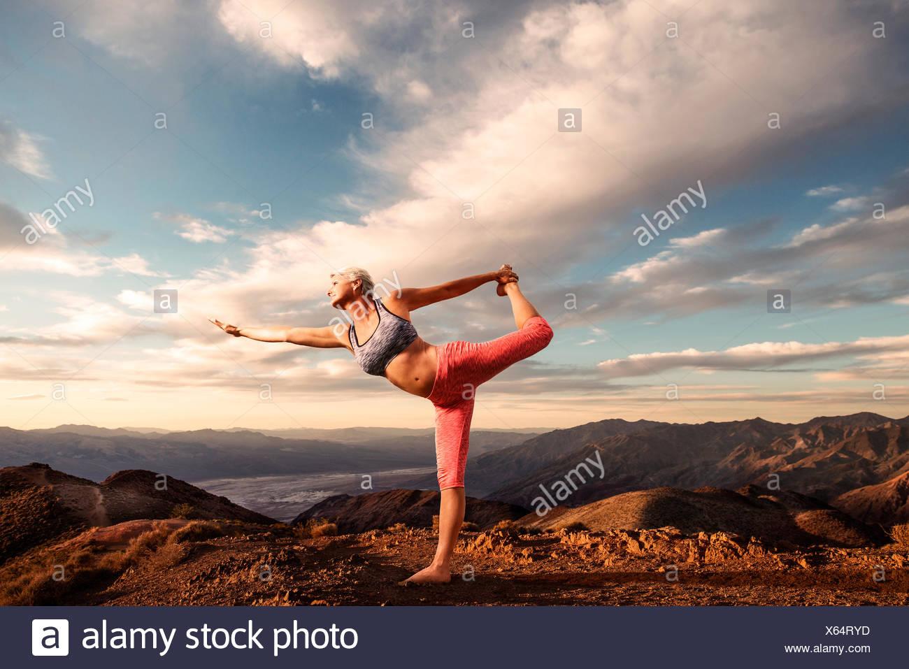 Senior donna fare yoga pone sulla cima della montagna al tramonto con il paesaggio deserto e la valle sottostante. Immagini Stock
