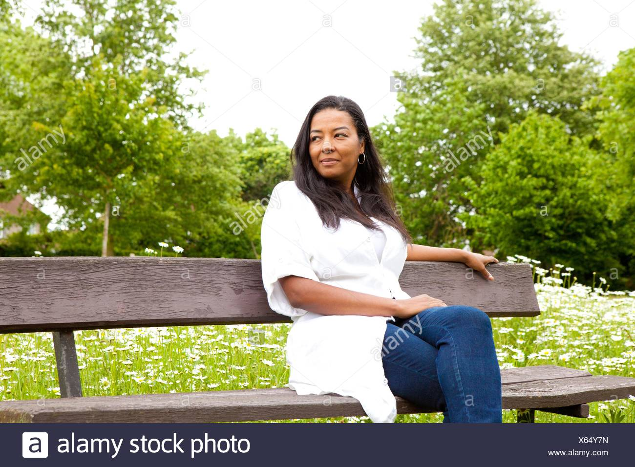 Donna matura guardando fuori da una panchina nel parco Immagini Stock