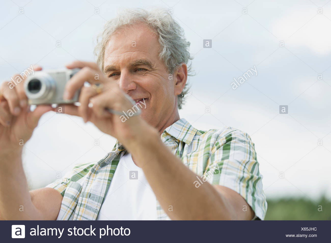 Attraente uomo senior concentrandosi videocamera all'esterno. Immagini Stock