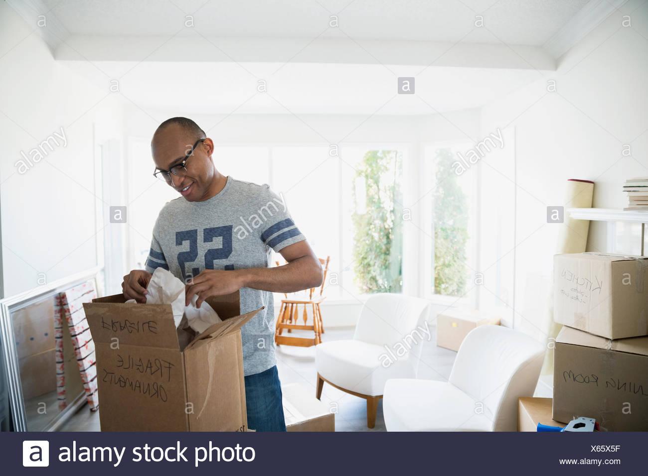 Uomo di imballaggio scatola movimento nel soggiorno Immagini Stock