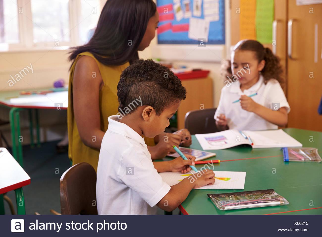 Femmina di insegnante di scuola elementare aiutare gli alunni a scrivania Immagini Stock