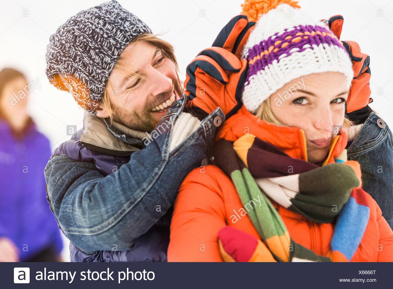 Uomo che fa orecchie di coniglietto dietro la donna che indossa knit hat Immagini Stock