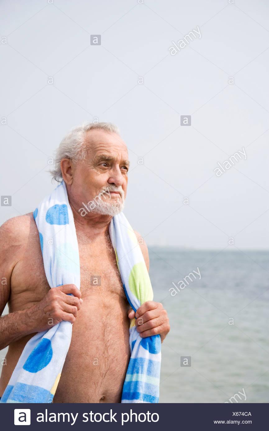 25187c356d07 Ritratto di un uomo anziano in un costume da bagno e asciugamano in spiaggia  Immagini Stock