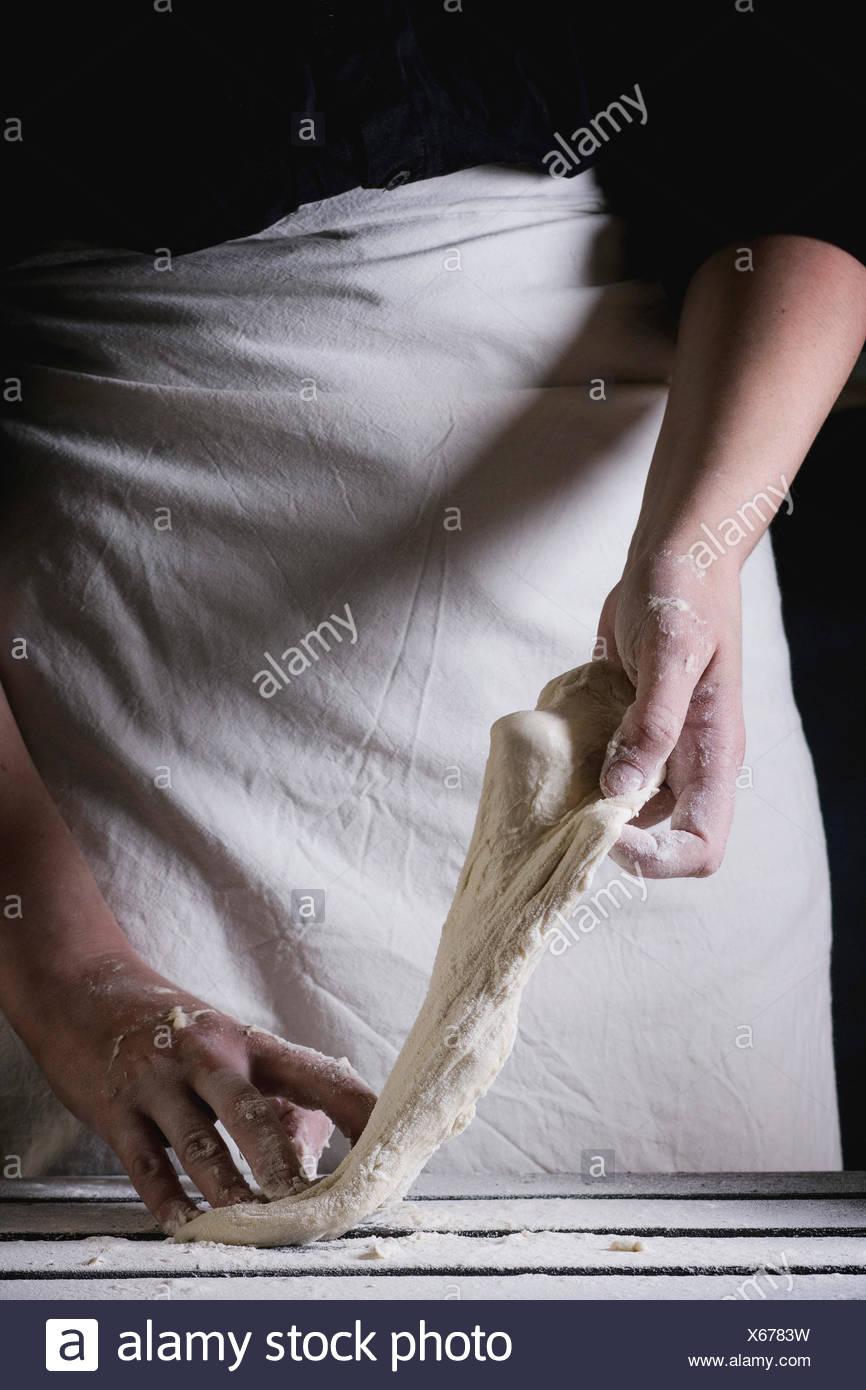 Le mani delle donne rendendo la pasta per pizza. Vedere serie Immagini Stock