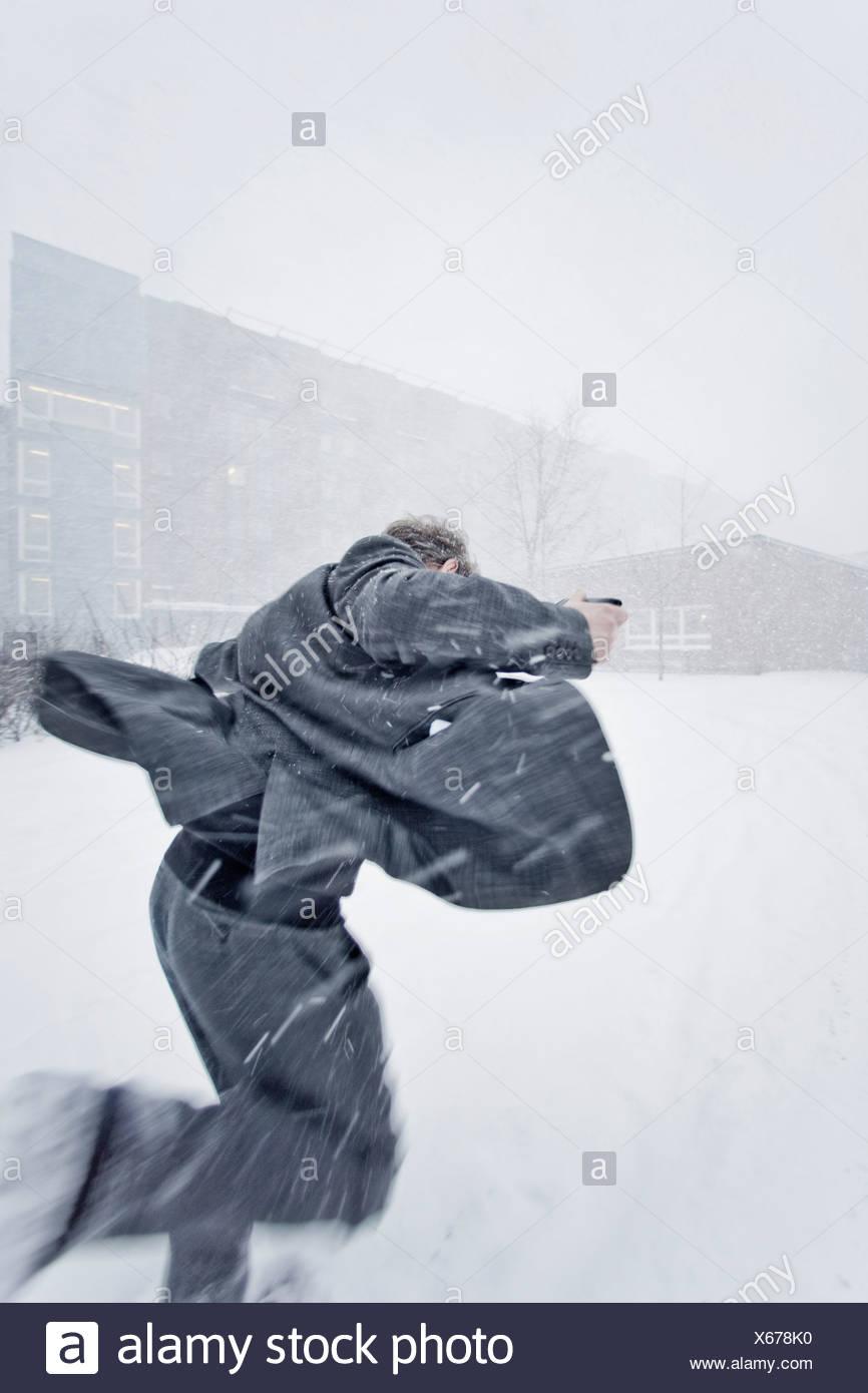 Uomo che corre nella neve Immagini Stock