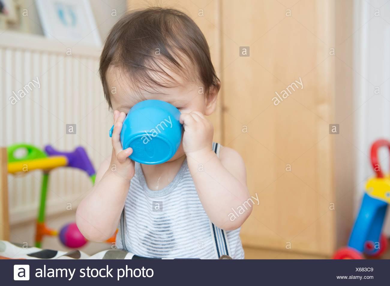 Bimbo a bere da baby cup in sala giochi Immagini Stock