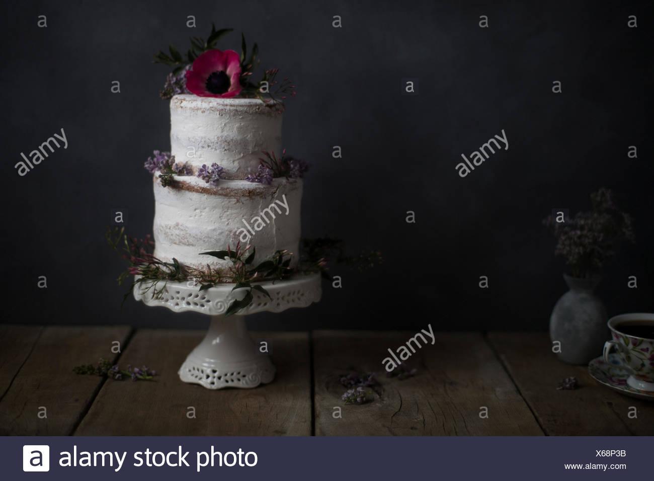 Torte fatte in casa, con decorazioni floreali, su di un supporto. Sfondo scuro. Immagini Stock