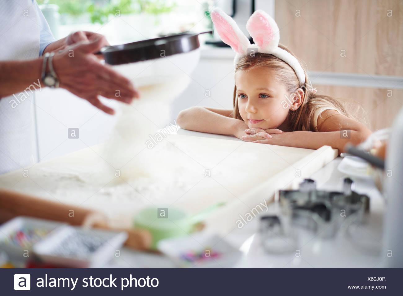 Ragazza Guarda la nonna setacciare la farina per la cottura di pasqua Immagini Stock
