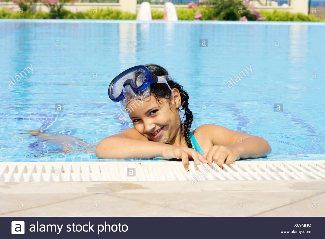 Carino sorridente bambina (6-7) avente fun in piscina Immagini Stock