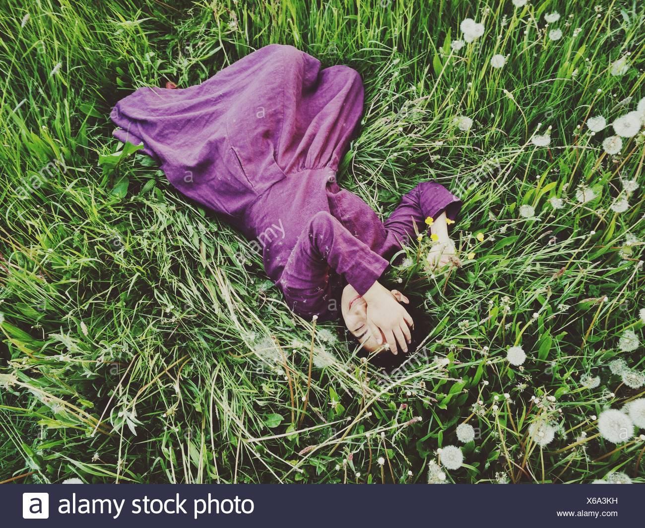 Vista in elevazione di una donna sdraiata in erba con la mano che copre il volto Immagini Stock