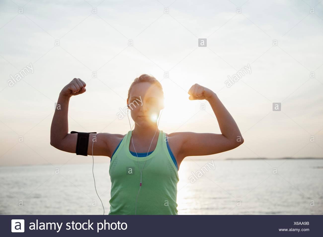 Donna che indossa il tracker di attività, braccia alzate la flessione di muscoli guardando la fotocamera Immagini Stock