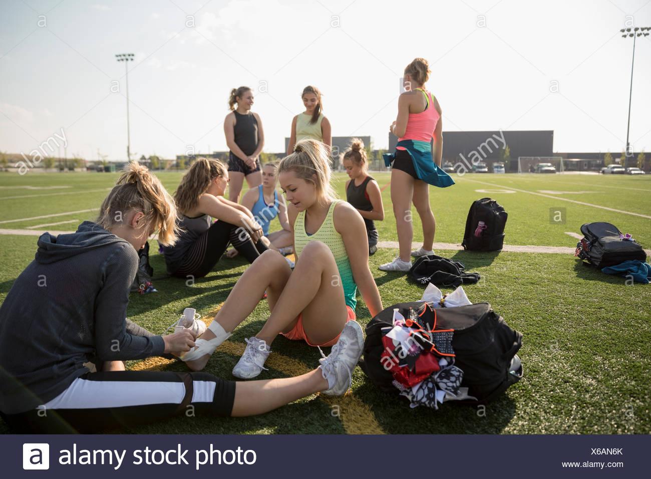 Ragazza adolescente high school cheerleader taping piede e caviglia con nastro adesivo sul soleggiato Campo di calcio Immagini Stock