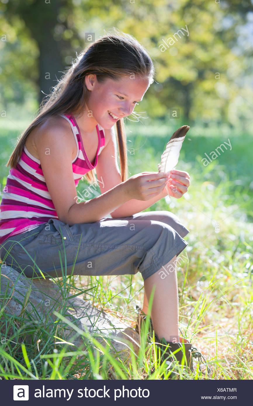Ragazza sorridente, guardando giù, seduta in campo orlate da alberi Immagini Stock