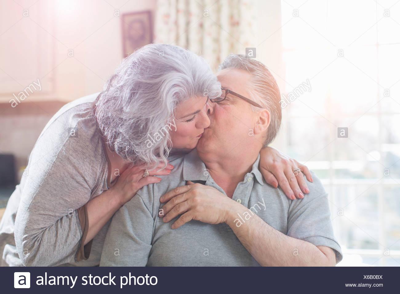 Affettuoso adulto giovane kissing a casa Immagini Stock