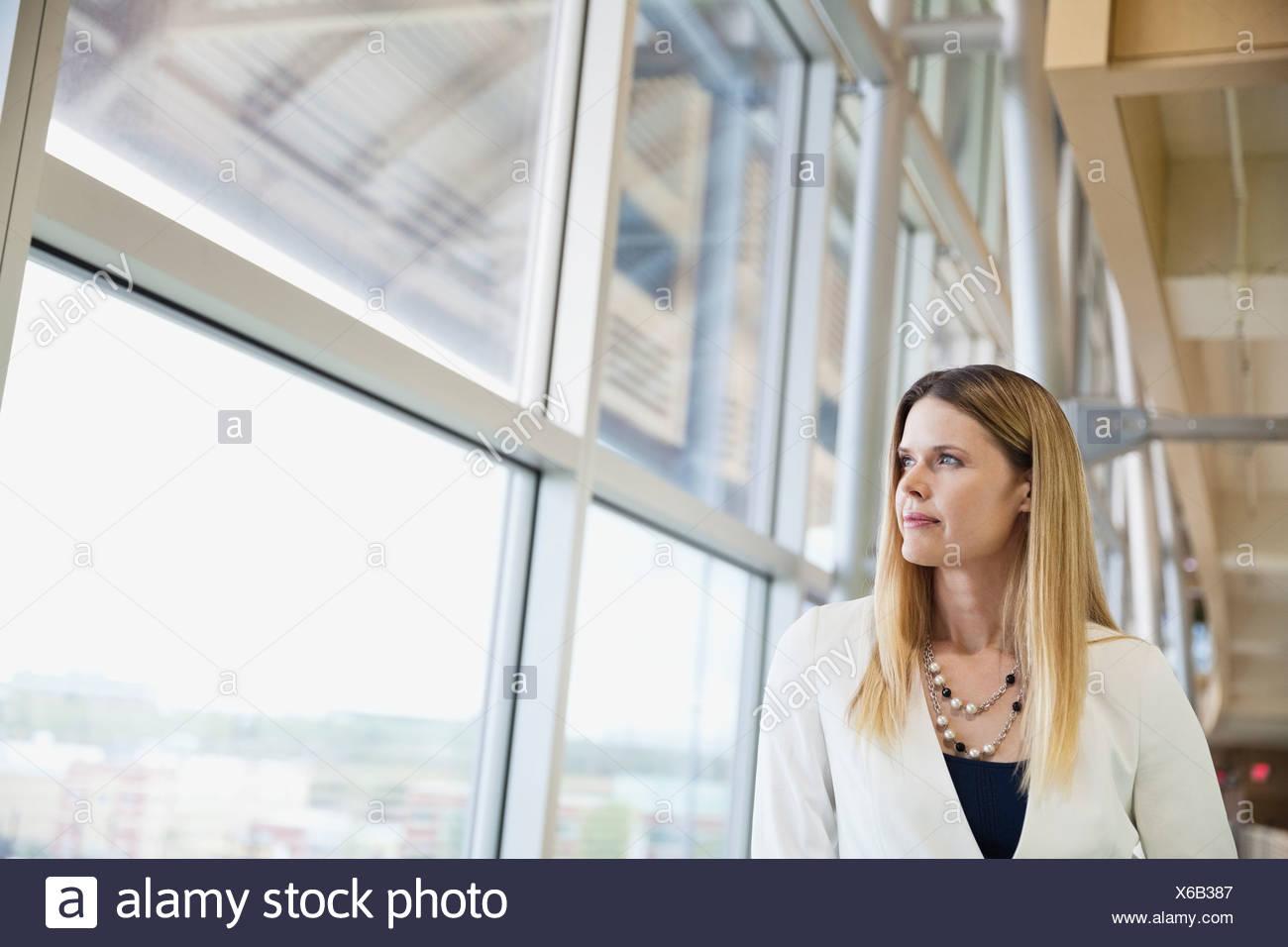 Riflessivo imprenditrice a guardare fuori dalla finestra Immagini Stock