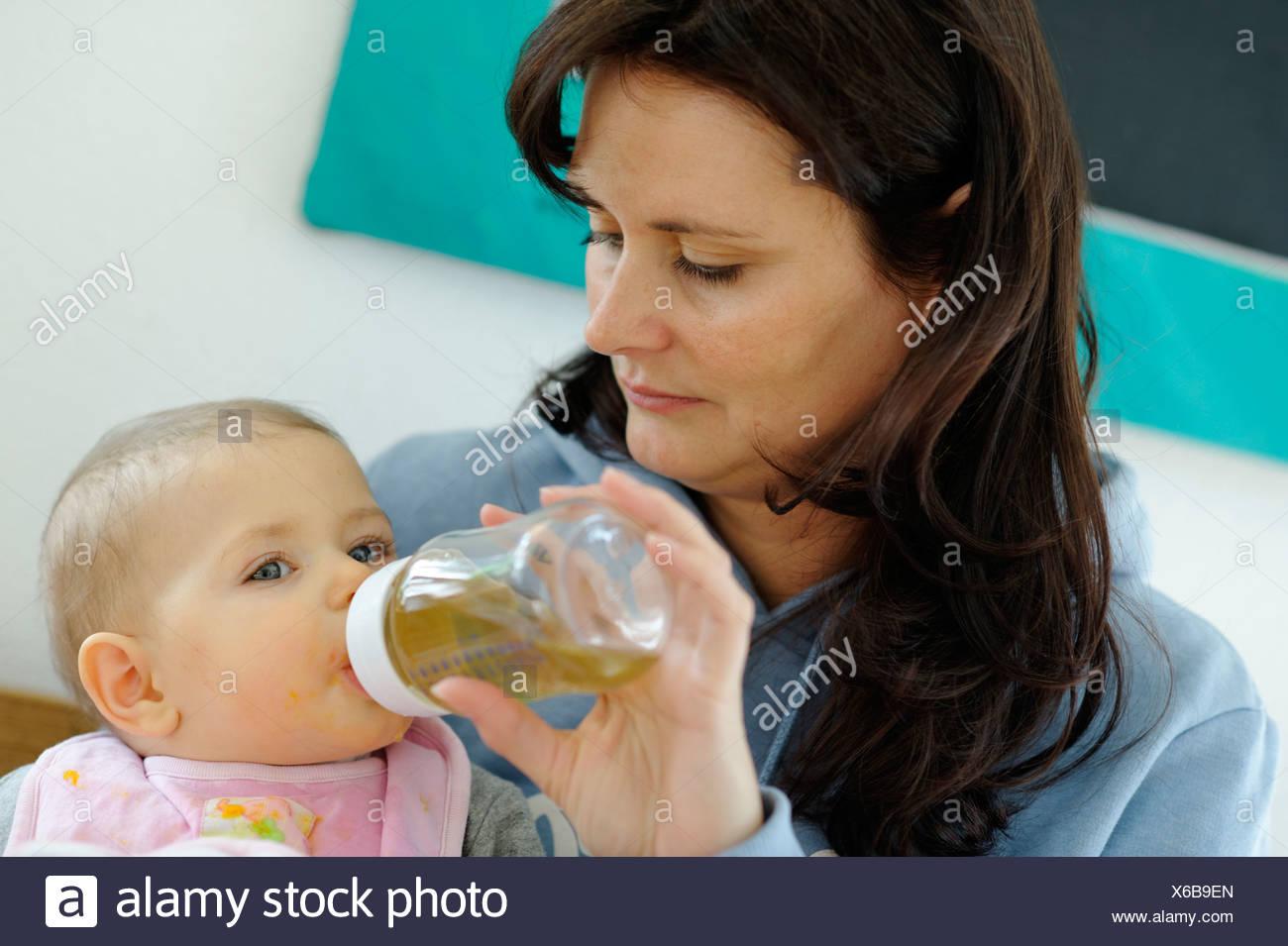 Baby, sei mesi, bere da una bottiglia tenuto da sua madre Immagini Stock